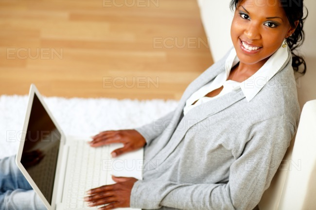 Young girl smiling at you with her laptop stock photo