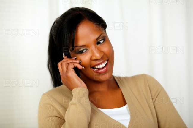 Young lady looking down while talking on cellphone stock photo