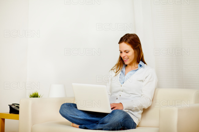 Young lady on sofa with a laptop stock photo