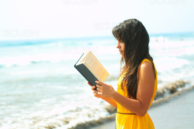 Young lady reading a book on the beach stock photo