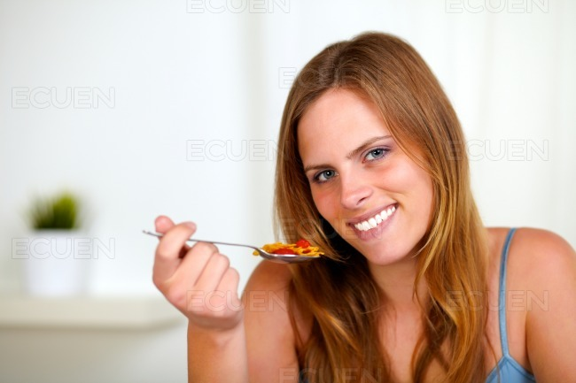 Young lovely woman eating breakfast stock photo
