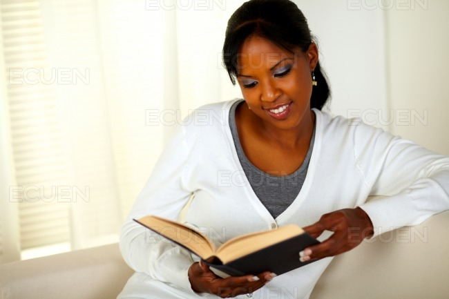 Young pretty woman browsing a book stock photo