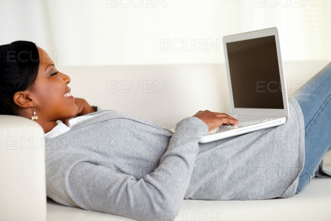 Young relaxed woman working on laptop stock photo