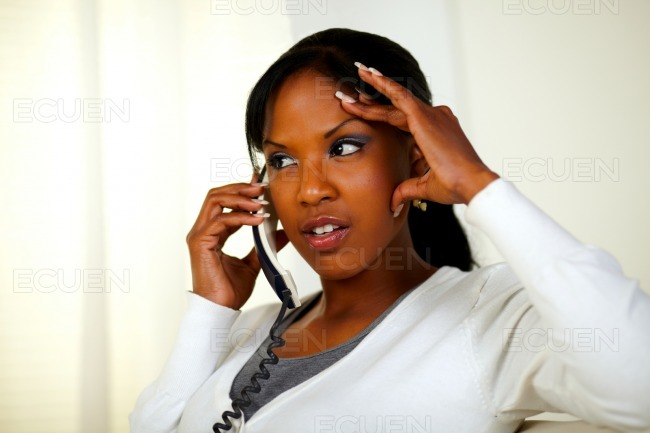 Young woman conversing on phone with headache stock photo