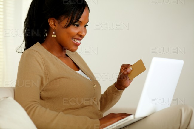 Young woman holding a gold credit card with laptop stock photo