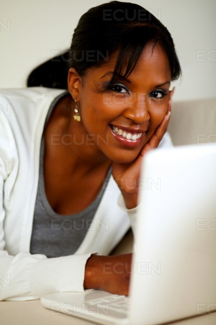 Young woman looking at you in front of her laptop stock photo