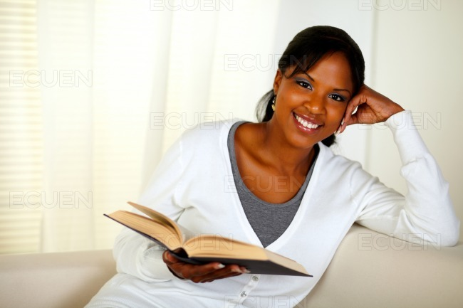 Young woman looking at you while holding a book stock photo
