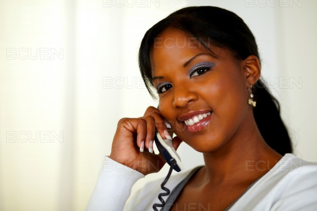 Young woman looking at you while talking on phone stock photo