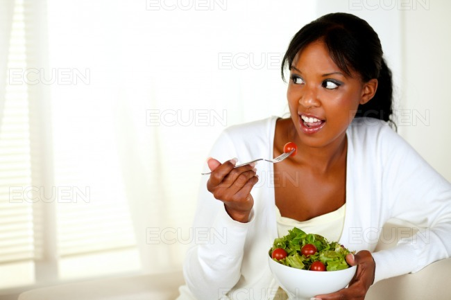 Young woman looking right as she eats her salad stock photo