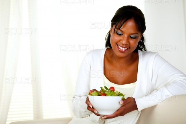 Young woman looking to a green salad bowl stock photo