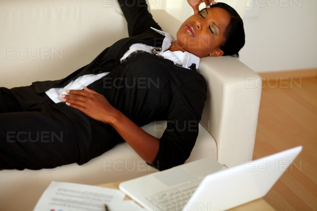 Young woman lying with eyes closed and headache stock photo