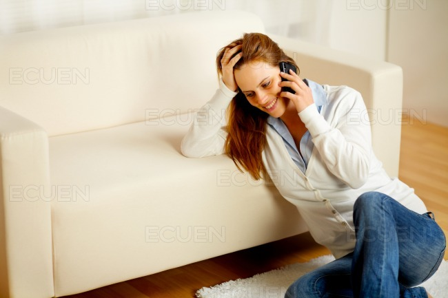 Young woman on mobile phone at home stock photo