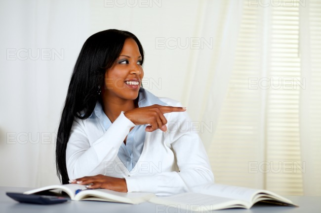 Young woman pointing and looking to his left stock photo