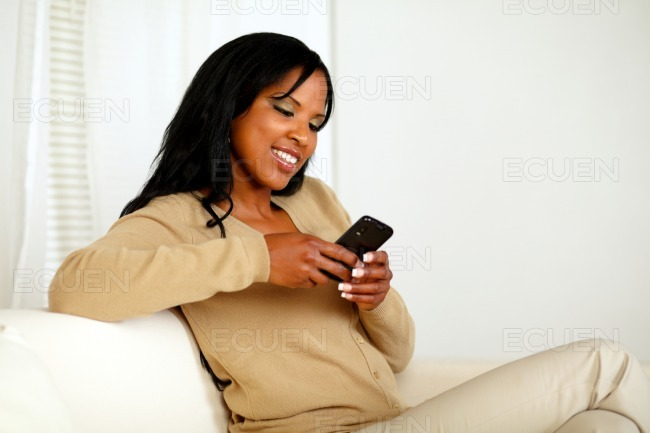 Young woman sending a message by the cellphone stock photo