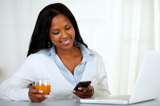 Young woman sending a message by the mobile stock photo