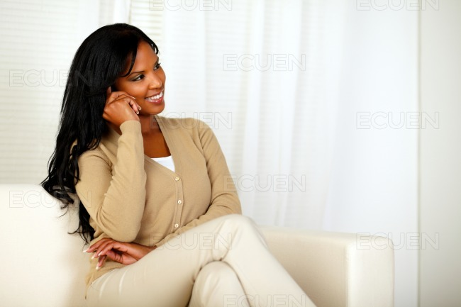 Young woman sitting on sofa talking on cellphone stock photo