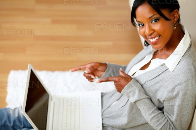 Young woman smiling at you and pointing her laptop stock photo