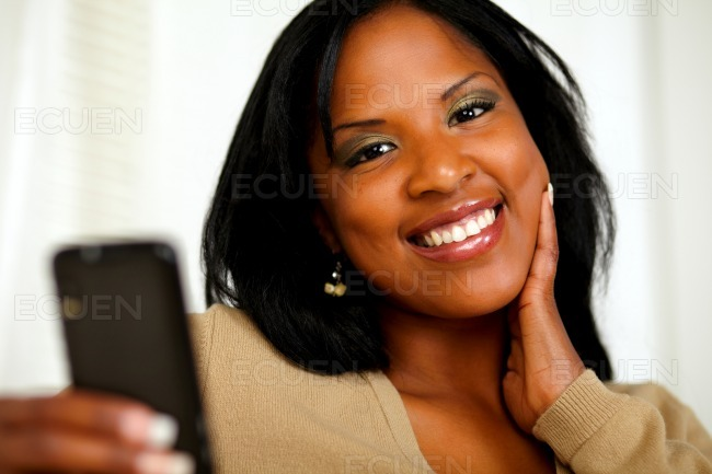 Young woman smiling at you while sending a message stock photo