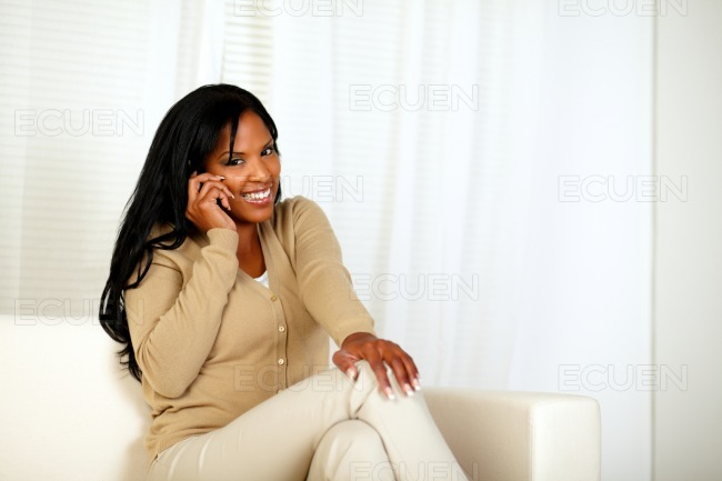 Young woman smiling at you while speaking on phone stock photo