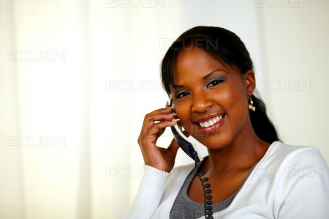 Young woman smiling at you while talking on phone stock photo