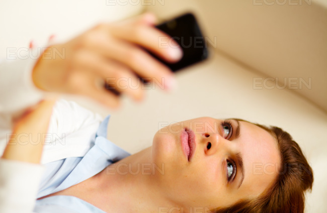 Young woman using a cellphone at home stock photo