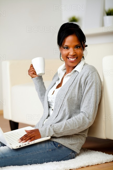 Young woman with a mug in front of her laptop stock photo