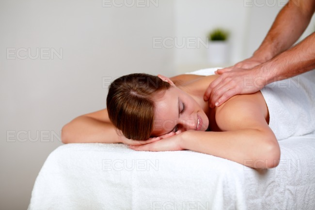 Young woman with eyes closed receiving a massage stock photo