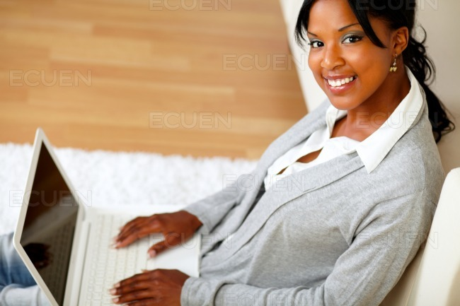Young woman with her laptop smiling at you stock photo