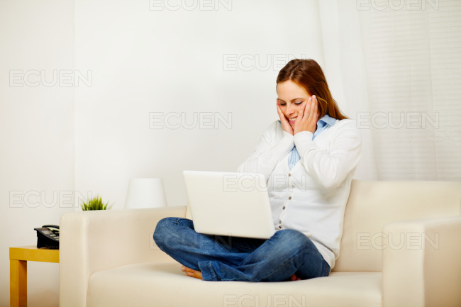 Young woman working on sofa with a laptop stock photo