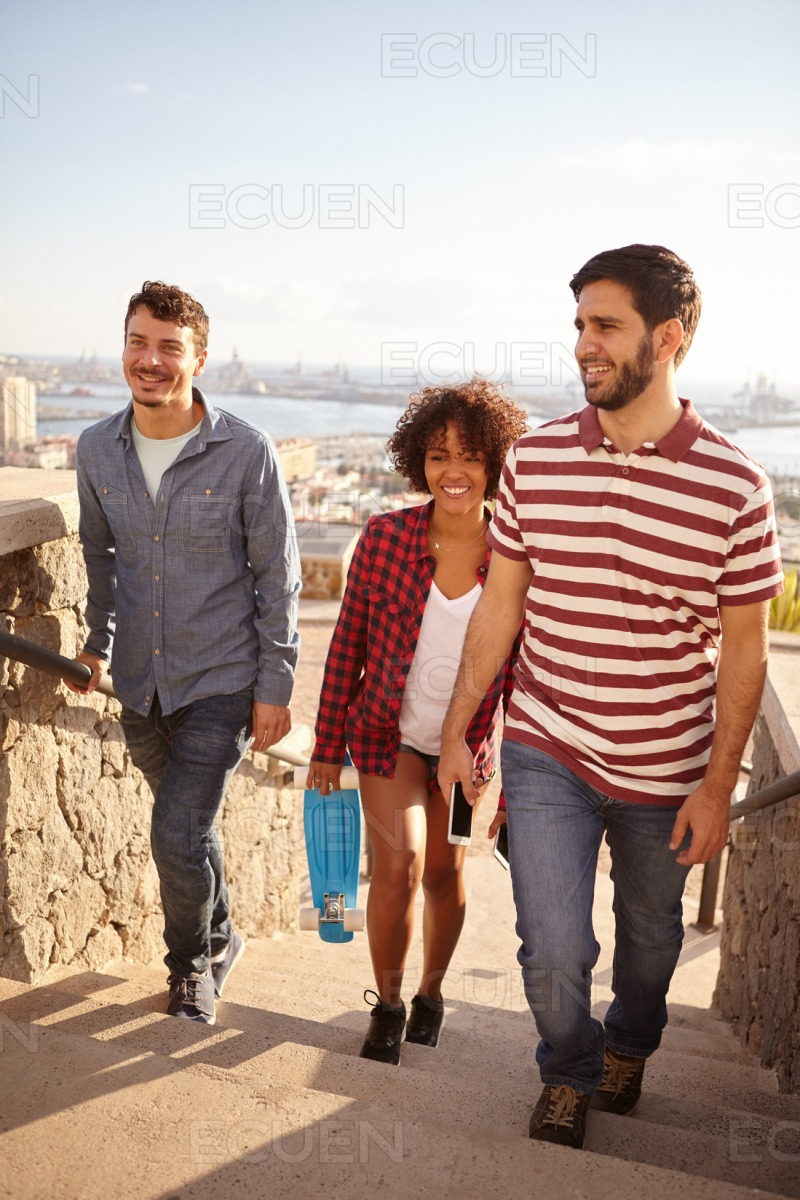 Happy chatty friends ascending the steps stock photo