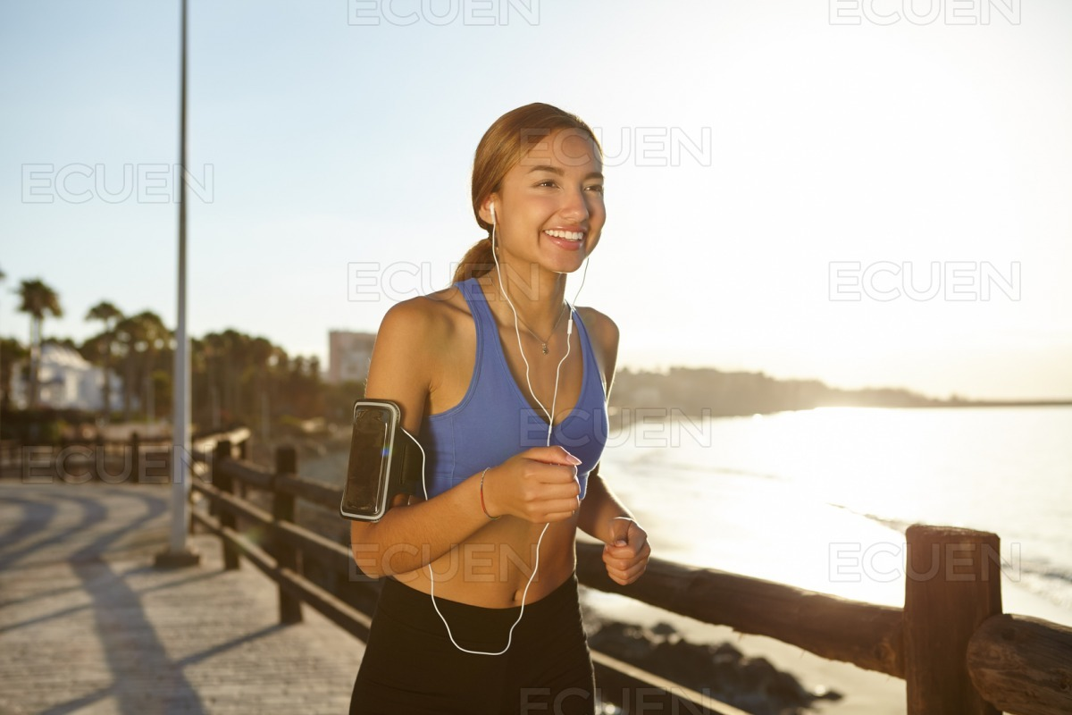 Happy runner woman jogging on the beach stock photo