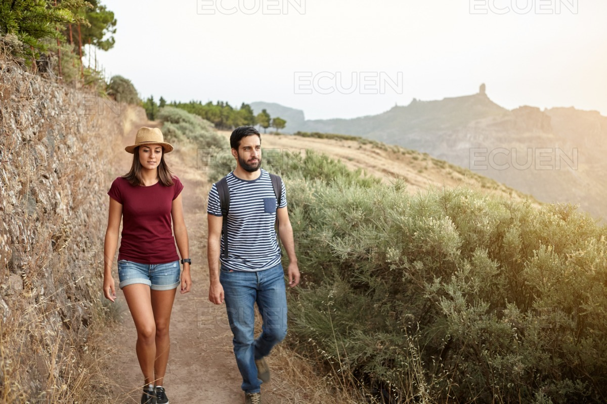 Young couple with backpack and straw hat stock photo