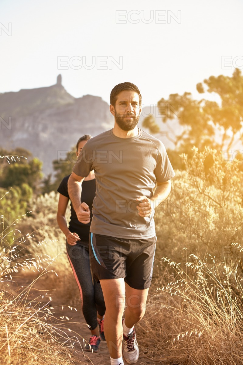 Young joggers with mountains behind them stock photo