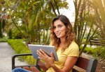 Beautiful woman using tablet while sitting in park