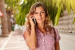Cheerful lady speaking on cell phone while walking
