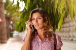 Cheerful woman speaking to cell phone outdoors