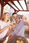 Couple taking selfie clinking their glasses