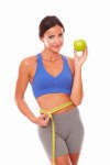 Fit latin woman showing apple for weight loss