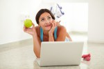 Fit woman holding apple while wondering