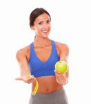 Fit woman holding fruit and measuring tape