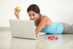 Fit woman with apple looking at computer
