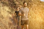 Gorgeous couple jogging in mountain path