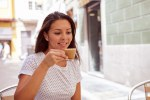 Happily smiling young girl drinking coffee