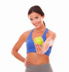 Lady in sportswear holding apple on left hand