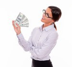 Pensive smiling brunette businesswoman with money