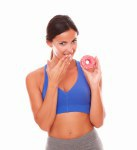 Slim adult female holding donut on left hand