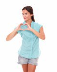 Smiling girl in short jeans making a love sign