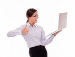 Smiling happy businesswoman holding a laptop