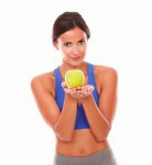 Smiling lady in sportswear holding apple