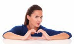 Smiling woman making a love sign